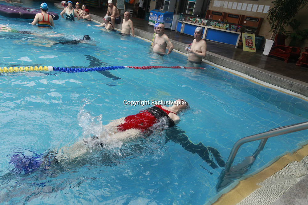 ANSHAN, CHINA - MARCH 18: (CHINA OUT) <br /> <br /> Swim With Arms And Legs Tied Up<br /> <br /> Li Yunfang, 59, weight 50 Kg, learns swimming with arms and legs tied up at a swimming pool on March 18, 2014 in Anshan, Liaoning Province of China. Li cost three months to learn the skill. She hopes to won a Guinness World Records. <br /> &copy;Exclusivepix