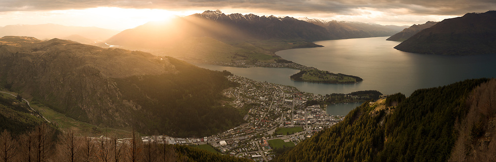 The sun pokes through clouds over this vista of Queenstown and Lake Wakatipu.