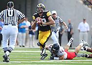September 19, 2009: Iowa quarterback Ricky Stanzi (12) gets tripped up by Arizona defensive end Ricky Elmore (44) during the Iowa Hawkeyes' 27-17 win over the Arizona Wildcats at Kinnick Stadium in Iowa City, Iowa on September 19, 2009.