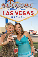 Two women in front of Welcome to Las Vegas sign