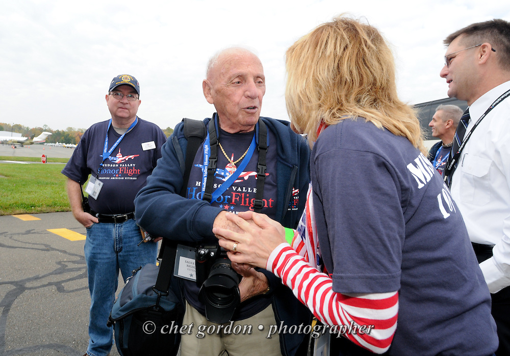 WWII Veterans and their escorts board a waiting charter flight at Westchester County Airport in White Plains, NY on Saturday, October 18, 2014. Seventy-five WWII Veterans from the Westchester County area toured the WWII Memorial and Arlington National Cemetery onboard the inaugural flight from Westchester County Airport in White Plains, NY. Hudson Valley Honor Flight is a chapter of the Honor Flight Network, which provides free flights for WWII Veterans and tours of the WWII Memorial constructed in their honor, and other sites in the nation's capital.  © www.chetgordon.com