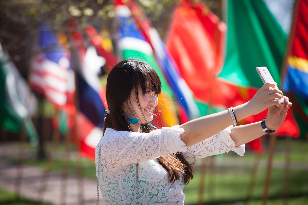 Ohio University student Wenqi Ma of China takes a selfie in font of the rows of flags on the college green during the celebration of International Week that culminated with a street fair Saturday April 19, 2014.  Photo by Ohio University / Jonathan Adams