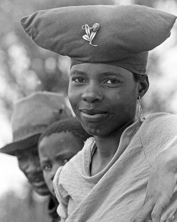 Botswana woman dressed in traditional headdress goes to market on wagon with men