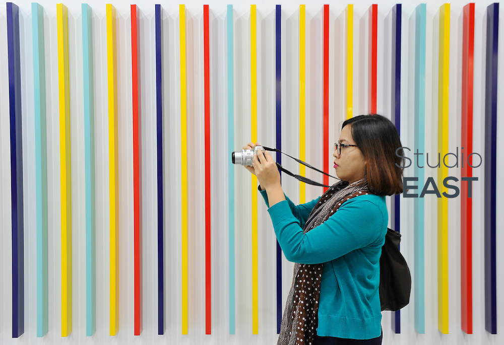 HONG KONG - MARCH 13:  A visitor takes a picture in front of sculpture 'Split Attraction' by Liam Gillick on the preview day of Art Basel art fair on March 13, 2015 in Hong Kong, Hong Kong.  (Photo by Lucas Schifres/Getty Images)