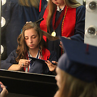 Nettleton High School senior Savannah Mills gets her hair be her classmate Morgan Kennedy before they head out for Saturday's graduation at the BancorpSouth Arena in Tupelo.
