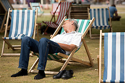 © Licensed to London News Pictures. 24/07/2013. Stratford upon Avon, Warwickshire, UK. As temperatures rise after the recent thunderstorms and rain, people flocked to Stratford upon Avon to start enjoying the sun. Taking a well earned  lunchtime break on the deck chairs by the river. Photo credit : Dave Warren/LNP