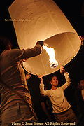 A man and a woman light a Lanna lantern, known as Khom Loy, (Loi) at the annual Loi Krathong Festival in Chiang Mai, Thailand. Thousands of lanterns fill the night skies each year, and the event is enjoyed by visitors and residents alike.