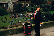 A young man has stopped by a rubbish bin to inspect his shoulder on which a nearby pigeon has recently messed on his best work suit. It is an unfortunate incident in the middle of a working day for this man in the heart of the City of London, London's financial centre - otherwise called The Square Mile. Armed with a spare tissue paper, the male cranes his neck over the shoulder to see how much of the crap remains while the flock of birds pace around on nearby grass to scavenge for crumbs left by other lunchtime office workers, otherwise enjoying warm weather in Bishopsgate Churchyard.