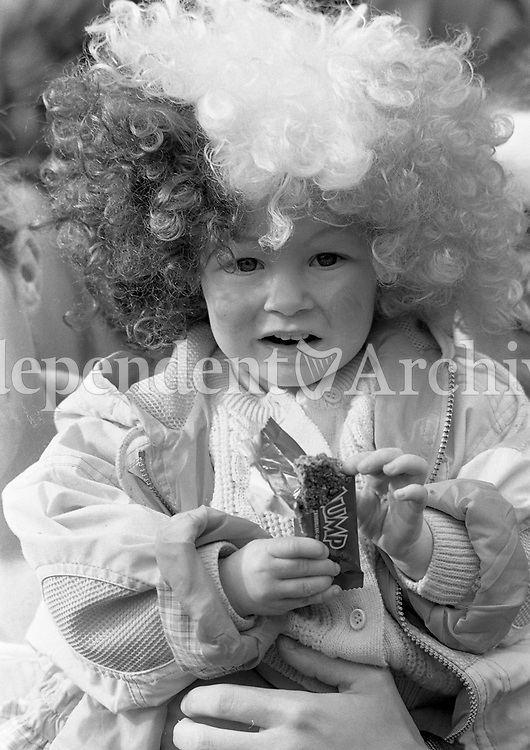 Sporting a Tri-Colour wig, 2 year old Haley McMahon from Clondalkin, has a chocolate bar at the St Patrick's Day Parade in O'Connell Street, Dublin, 17/03/1997 (Part of the Independent Newspapers Ireland/NLI Collection).