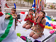 "03 DECEMBER 2011 - PHOENIX, AZ:    Children in a float pray during a procession in Phoenix to honor the Virgin of Guadalupe. The Phoenix diocese of the Roman Catholic Church held its Sixth Annual Honor Your Mother Day Saturday to honor the Virgin of Guadalupe. According to Mexican Catholic tradition, on December 9, 1531 Juan Diego, an indigenous peasant, had a vision of a young woman while he was on a hill in the Tepeyac desert, near Mexico City. The woman told him to build a church exactly on the spot where they were standing. He told the local bishop, who asked for some proof. He went back and had the vision again. He told the lady that the bishop wanted proof, and she said ""Bring the roses behind you."" Turning to look, he found a rose bush growing behind him. He cut the roses, placed them in his poncho and returned to the bishop, saying he had brought proof. When he opened his poncho, instead of roses, there was an image of the young lady in the vision. The Virgin is now honored on Dec 12 in Catholic churches throughout Latin America and in Hispanic communitied in the US.   PHOTO BY JACK KURTZ"