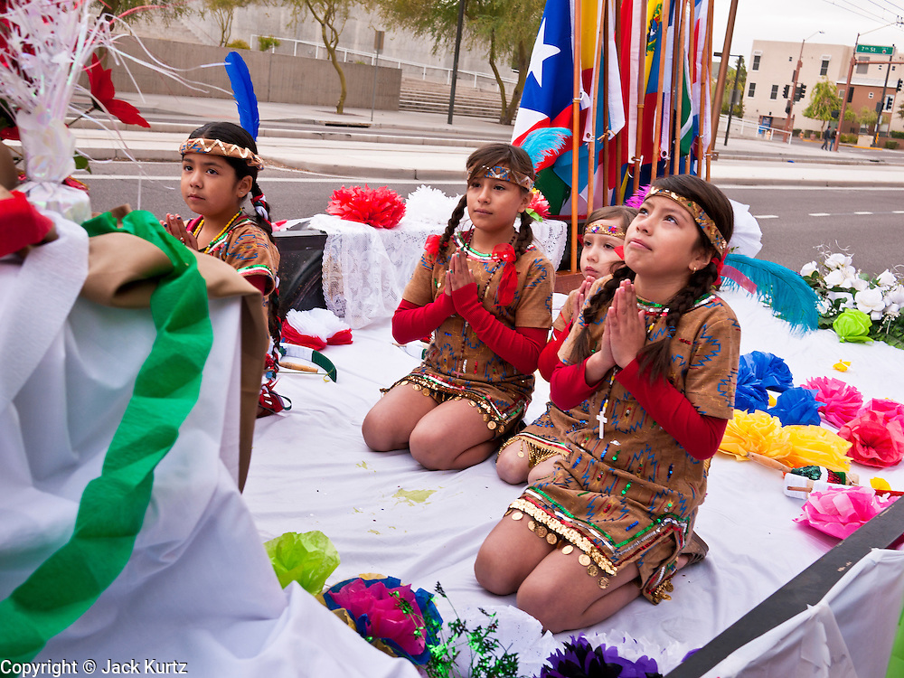 """03 DECEMBER 2011 - PHOENIX, AZ:    Children in a float pray during a procession in Phoenix to honor the Virgin of Guadalupe. The Phoenix diocese of the Roman Catholic Church held its Sixth Annual Honor Your Mother Day Saturday to honor the Virgin of Guadalupe. According to Mexican Catholic tradition, on December 9, 1531 Juan Diego, an indigenous peasant, had a vision of a young woman while he was on a hill in the Tepeyac desert, near Mexico City. The woman told him to build a church exactly on the spot where they were standing. He told the local bishop, who asked for some proof. He went back and had the vision again. He told the lady that the bishop wanted proof, and she said """"Bring the roses behind you."""" Turning to look, he found a rose bush growing behind him. He cut the roses, placed them in his poncho and returned to the bishop, saying he had brought proof. When he opened his poncho, instead of roses, there was an image of the young lady in the vision. The Virgin is now honored on Dec 12 in Catholic churches throughout Latin America and in Hispanic communitied in the US.   PHOTO BY JACK KURTZ"""