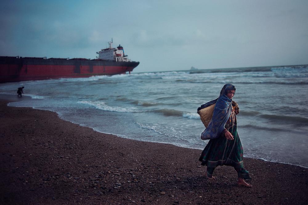 A woman walks along the beach searching for scrap metal at the Gaddani Ship Breaking Yard, Balochistan Province, Pakistan on August 16, 2011.