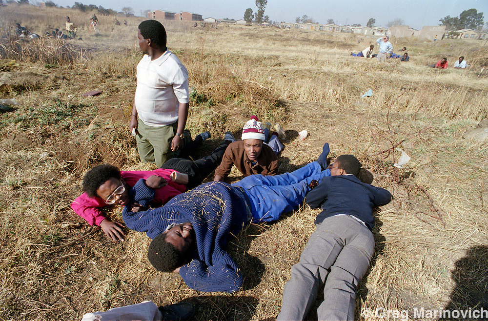 Boipatong, Vaal, Transvaal, South Africa 1992, June. ANC supporters lie wounded and or taking cover as police and ANC self defence units exchange fire in the aftermath of President FW de Klerks visit several days after the killing of 41 people by Inkatha warriors said to be supported by police.