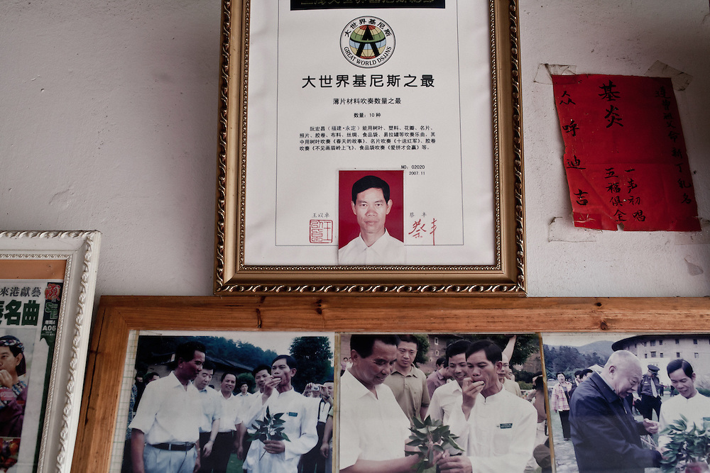 A local celebrity of Yongding... knows how to improve life of plants by playing music... On th e wall his diploma and pictures with officials.