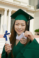 Graduate holding diploma and medal outside university portrait