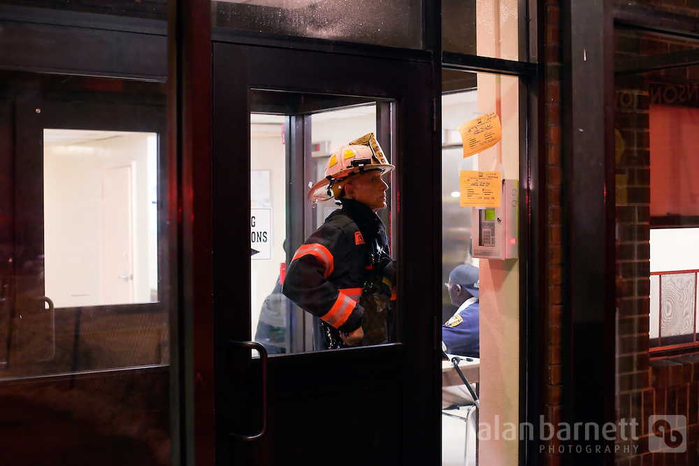 A battalion chief resets the alarm box at a housing complex.