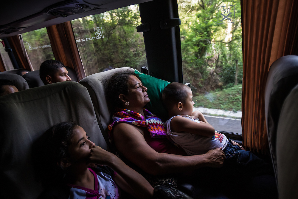 AGUA CALIENTE, HONDURAS - MAY 27, 2014:  Connie, who works making and selling tortillas, looks out of the window during a 10-hour bus ride from San Pedro Sula to Guatemala City.  She is migrating north without a visa, with all five of her children, because members of the Mara-18 gang have threatened to kill her oldest son. To leave Honduras with her children, corrupt immigration officials at the Aguas Calientes border crossing systematically required her and every other parent on the bus without required paperwork, to pay them a bribe of $50 per child for permission to take them out of the country. The manager of the bus line estimated over 80 percent of this route's passengers are migrants headed north, trying to enter the United States illegally. PHOTO: Meridith Kohut for The New York Times