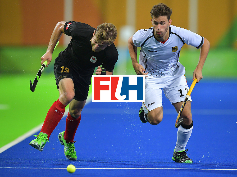 Germany's Timm Herzbruch chases the ball next to Canada's Mark Pearson during the men's field hockey Canada vs Germany match of the Rio 2016 Olympics Games at the Olympic Hockey Centre in Rio de Janeiro on August, 6 2016. / AFP / Carl DE SOUZA        (Photo credit should read CARL DE SOUZA/AFP/Getty Images)