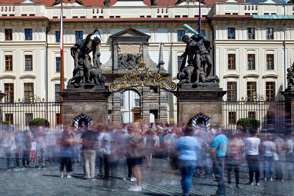 """Crowds in-front of the Wrestling Titans (Sousoší Souboj Titánů), also known as Fighting Giants and Giants' Gate, which are pair of outdoor sculptures leading to the first courtyard of Prague Castle at """"Hradcany Square"""" (Hradcanske Namesti)."""