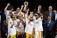 17 June 2010:  Guard Derek Fisher of Los Angeles Lakers holds up the Larry O'Brien NBA Championship Trophy as Kobe Bryant holds up the Bill Russell Finals MVP Trophy as teammates celebrate after the Lakers defeat the Boston Celtics 83-79 and win the NBA championship in Game 7 of the NBA Finals at the STAPLES Center in Los Angeles, CA.
