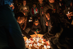 "© Licensed to London News Pictures . 01/12/2013 . Manchester , UK . People place candles in memory of loved ones , in the park . World AIDS Day commemoration in Sackville Park , Manchester , this evening (Sunday 1st December 2013) including a candle-lit procession around the city's "" Gay Village "" . Photo credit : Joel Goodman/LNP"