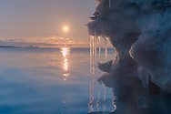 A small iceberg floats near the shore, in Longyearbyen, Svalbard, while the midnight sun shines right above the horizon.