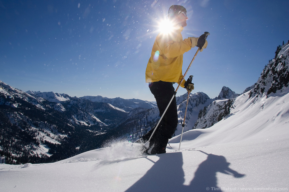 A caucasian man hikes on snowshoes in the winter near Snoqualmie Pass, Washington.