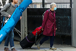 © Licensed to London News Pictures. 01/02/2020. London, UK. A woman with suitcase arrives at Paddington Station from Heathrow Airport wearing a surgical face mask following the outbreak of Coronavirus in Wuhan, China. According to Twitter two people were taken to hospital from Paddington Station on the evening of Friday 31 January, amid fears that Coronavirus has speed to London. Part of the station was cordoned off following a woman sitting on a bench, while staff in face masks keep guard. Photo credit: Dinendra Haria/LNP