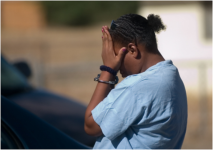 Michael Stenerson / Staff Photographer.Latisha Davis covers her face before she is transported to jail during a search warrant sweep Thursday morning in Adelanto. Davis tried to buy drugs from a house that was being searched by Sheriff's deputies.