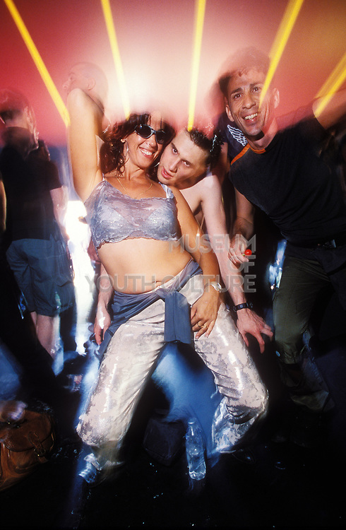 Three clubbers having a good time on the dancefloor of a club, UK 2000's