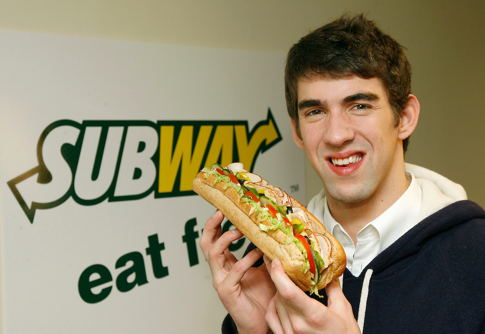 In this photo from Subway, world champion swimmer Michael Phelps sinks his teeth in to a foot long Subway sandwich after signing a contract which seals a long-term partnership with Subway, New York, Tuesday, Nov. 18, 2008. Phelps will be representing the brand across all marketing channels and joins an impressive list of athlete partners that have included Michael Strahan, Ryan Howard, Kimmie Meissner, Tony Parker, Laila Ali and Reggie Bush. (Photo/Subway/Stuart Ramson)
