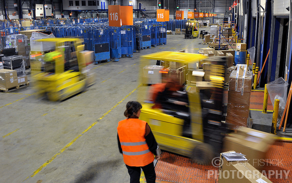 TNT employees move packages by forklift truck at the TNT NV delivery depot in Brussels, Belgium, on Thursday, Feb. 12, 2009. (Photo © Jock Fistick)