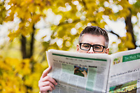 Portrait of mature attractive man sitting on bench while reading newspaper in park