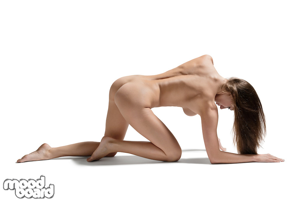 Young naked woman crawling over white background