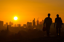 London, October 27 2017. Walkers on Primrose hill are silhouetted against the rising sun as the day breaks over London's skyline. © Paul Davey