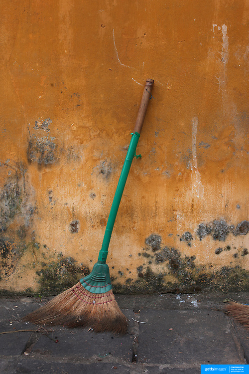 A brush leans against a bright yellow wall in Hoi An, Vietnam. Hoi An is an ancient town and an exceptionally well-preserved example of a South-East Asian trading port dating from the 15th century. Hoi An is now a major tourist attraction because of its history. Hoi An, Vietnam. 5th March 2012. Photo Tim Clayton