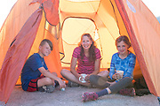 Mother and children having coffee and cocoa in tent during sunrise while camping at the City of Rocks National Reserve in Southern Idaho between Almo and Oakley, Idaho. MR