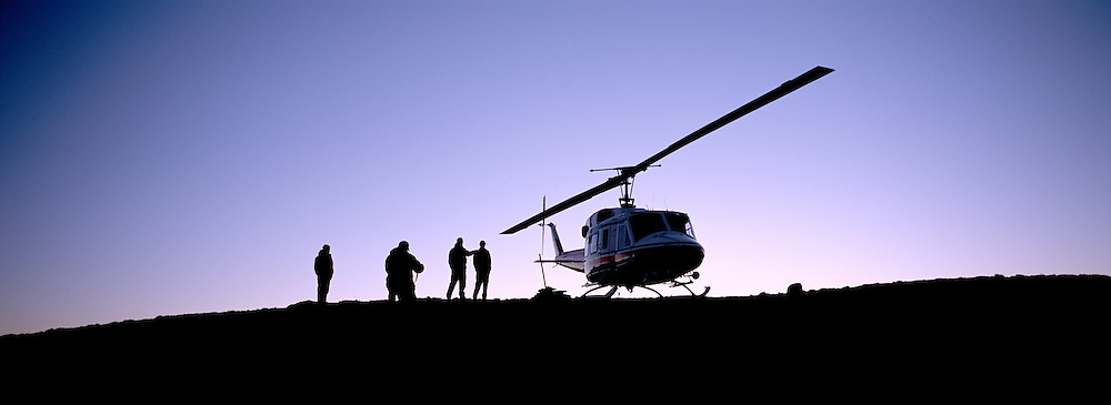 Helicopter in silhouette on top of mountain