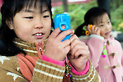 Elementary school children use KDDI Corp.'s mamorino mobile phone in Tokyo, Japan on Nov. 22, 2009. .Photographer: Robert Gilhooly