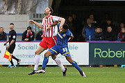 Lyle Taylor of AFC Wimbledon and Jamie McCombe of Stevenage tussle during the Sky Bet League 2 match between AFC Wimbledon and Stevenage at the Cherry Red Records Stadium, Kingston, England on 12 December 2015. Photo by Stuart Butcher.