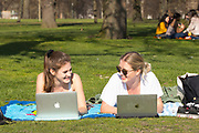 UNITED KINGDOM, London: 26 February 2019. Lucy Cockerell 24 (left) and Matilda Catani 23 (right) enjoy working outdoors in Kensington Gardens on what is set to be the warmest day in February since records began. Temperatures are set to reach up to 20 degrees Celsius in the capital today. Rick Findler / Story Picture Agency