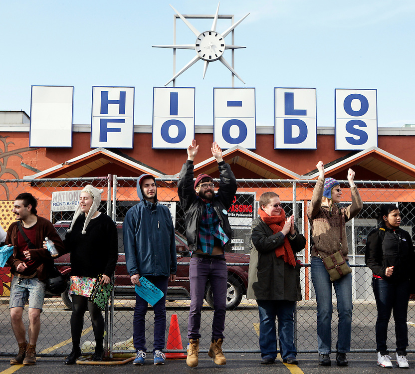 """(20110402, Jamaica Plain, Massachusetts)..Ben Mauer, center, jumping, of """"Whose Foods,"""" protests in front of Hi-Lo Foods, a Jamaica Plain staple for 47 years, which will be the location of a new Whole Foods Market in Jamaica Plain, Massachusetts on Saturday, April 2, 2011.  """"Whose Foods,"""" the rally's organizer, contends that the Whole Foods Market would price out lower-income families and reduce the diversity of the neighborhood...Photo by Brooks Canaday."""