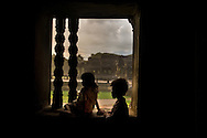 A flash storm hits Angor Wat as children take refuge in a temple.