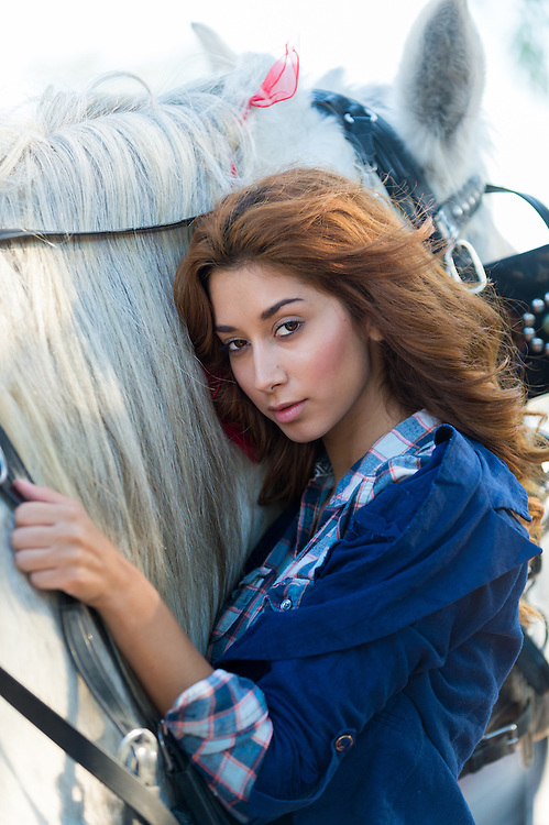 Beautiful sultry woman with long brunette hair standing alongside a horse looking at the camera