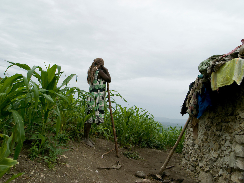 A woman stands between her home and a corn field. Small scale agriculture provides at least 60 percent of the population with work in Haiti.