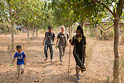 ICS volunteers Tania Tuzizila, Luna Boran & Keira Thompson use a large stick to pick mangos with the children in the garden of their host home, in the village of in Banteay Char, near Battambang, Cambodia.