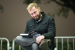 "© Licensed to London News Pictures . 03/11/2017 . Manchester , UK . A man reads a copy of Tommy Robinson's (real name Stephen Yaxley-Lennon ) book at the launch of the former EDL leader's book "" Mohammed's Koran "" at Castlefield Bowl . Originally planned as a ticket-only event at Bowlers Exhibition Centre , the launch was moved at short notice to a public location in the city . Photo credit : Joel Goodman/LNP"