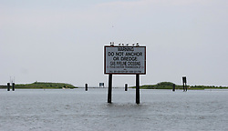 06 June 2010. Barataria Bay to Grand Isle, Jefferson/Lafourche Parish, Louisiana. <br /> Warning signs cross the marshes where petro chemical and gas pipelines criss cross the Louisiana wetlands. Oil companies have cut pipeline throughout the region. Ecologists argue this reckless carving up of the wetlands are one of the main reasons for erosion and salt water intrusion. The ecological and economic impact of BP's oil spill is devastating to the region. Oil from the Deepwater Horizon catastrophe is evading booms laid out to stop it thanks in part to the dispersants which means the oil travels at every depth of the Gulf and washes ashore wherever the current carries it. The Louisiana wetlands produce over 30% of America's seafood and are the most fertile of their kind in the world.<br /> Photo; Charlie Varley/varleypix.com