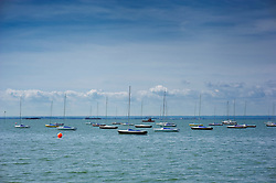 Sailing yachts and boats moored in the Thames estuary at Southend-on-Sea, Essex, England, UK.