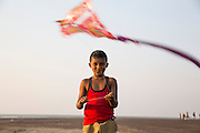 A young Indian boy plays with his kite on the beach.